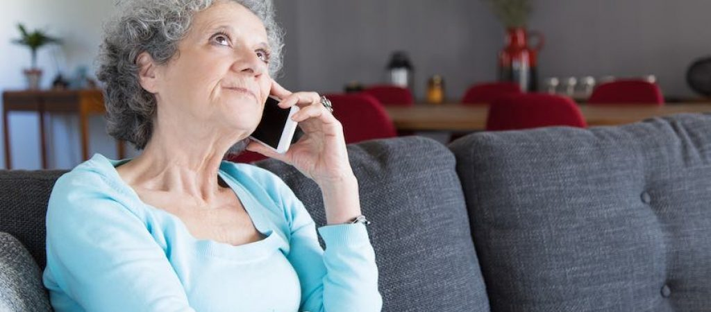 Portrait of pensive senior woman talking on mobile phone. Grandma sitting on couch at home and communicating via cellphone. Communication and retirement concept